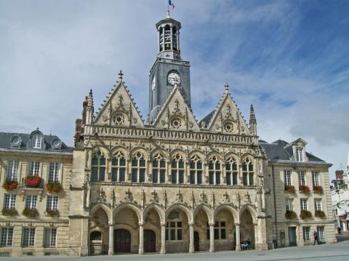 Ратуша в Сен-Кантене с богатым декором, башней по центру фасада, готический архитектурный стиль.