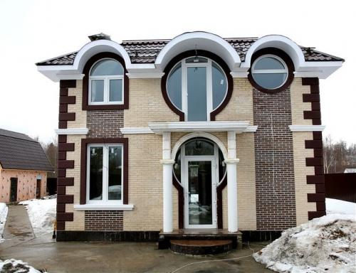 Фасад дома с овальными окнами.